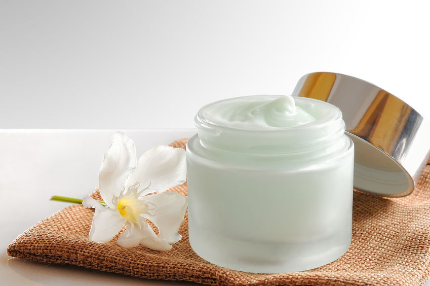 40812582 - glass open jar with facial or body cream on burlap. with lid and flower.isolated background. front view.